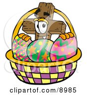 Wooden Cross Mascot Cartoon Character In An Easter Basket Full Of Decorated Easter Eggs