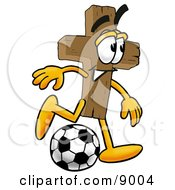 Clipart Picture Of A Wooden Cross Mascot Cartoon Character Kicking A Soccer Ball by Toons4Biz