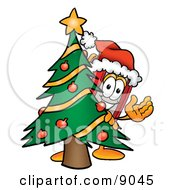 Clipart Picture Of A Red Book Mascot Cartoon Character Waving And Standing By A Decorated Christmas Tree