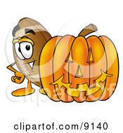 Clipart Picture Of A Football Mascot Cartoon Character With A Carved Halloween Pumpkin by Toons4Biz