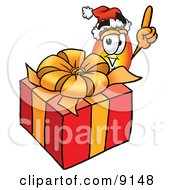 Clipart Picture Of A Flame Mascot Cartoon Character Standing By A Christmas Present