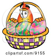 Clipart Picture Of A Flame Mascot Cartoon Character In An Easter Basket Full Of Decorated Easter Eggs