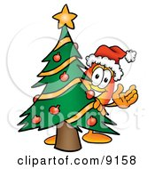 Clipart Picture Of A Flame Mascot Cartoon Character Waving And Standing By A Decorated Christmas Tree