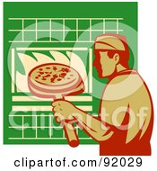 Male Chef Putting A Pizza In An Oven