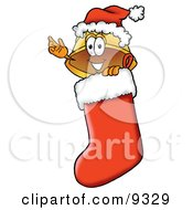 Clipart Picture Of A Hard Hat Mascot Cartoon Character Wearing A Santa Hat Inside A Red Christmas Stocking by Toons4Biz