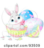 Adorable Easter Bunny Sitting In A Broken Striped Egg Shell