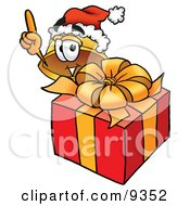 Clipart Picture Of A Hard Hat Mascot Cartoon Character Standing By A Christmas Present