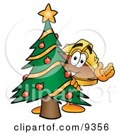 Hard Hat Mascot Cartoon Character Waving And Standing By A Decorated Christmas Tree by Toons4Biz