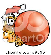 Hard Hat Mascot Cartoon Character Wearing A Santa Hat Standing With A Christmas Bauble by Toons4Biz