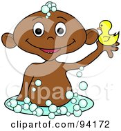 Hispanic Baby Holding Up A Rubber Duck In A Bubble Bath