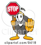 Clipart Picture Of A Hockey Puck Mascot Cartoon Character Holding A Stop Sign