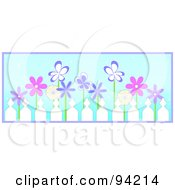 Row Of Pink And Purple Spring Flowers Behind A Picket Fence Over Blue With Purple Trim