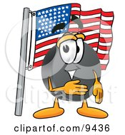 Clipart Picture Of A Hockey Puck Mascot Cartoon Character Pledging Allegiance To An American Flag by Toons4Biz
