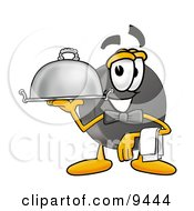 Hockey Puck Mascot Cartoon Character Dressed As A Waiter And Holding A Serving Platter