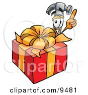 Clipart Picture Of A Hammer Mascot Cartoon Character Standing By A Christmas Present by Toons4Biz