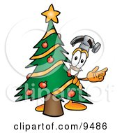 Hammer Mascot Cartoon Character Waving And Standing By A Decorated Christmas Tree by Toons4Biz