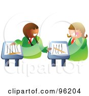 Two School Girls Chatting At Their Desks In Class