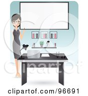 Beautiful Secretary Pointing To A Blank Board Behind Her Desk