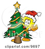 Clipart Picture Of A Light Bulb Mascot Cartoon Character Waving And Standing By A Decorated Christmas Tree