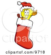 Light Bulb Mascot Cartoon Character Wearing A Santa Hat Inside A Red Christmas Stocking